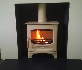 Charnwood C5 Woodburner in Almond - with a honed granite hearth and charcoal painted chamber in Guildford, Surrey.