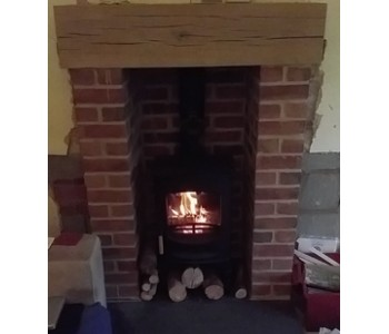 Charnwood C4 Woodburner with Store Stand - antique granite hearth, brick pillars and chamber with bespoke oak beam installed in Warwickshire.