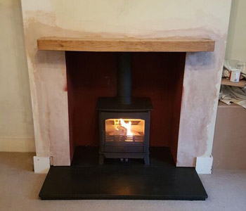 ACR Earlswood Multifuel Stove -installed with granite hearth and bespoke locally sourced oak beam in Guildford, Surrey.