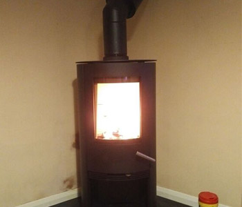 Termatec TT20R  woodburner in black - with bespoke, made to template honed black granite hearth installed in Reigate, Surrey.