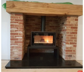 Stovax Studio 1 Freestanding Woodburner on bench installed to pumice lined chimney, polished granite hearths, brick pillars and locally sourced oak beam near Weybridge, Surrey