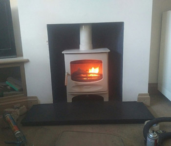 Charnwood Stove C5 wood burner in Almond - with a new section of internal factory made metal chimney system in Guildford, Surrey