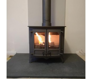 Charnwood Stoves Island - 2 stove in gun metal with green slate hearth and oyster Vlaze heat shield along with internal chimney system.