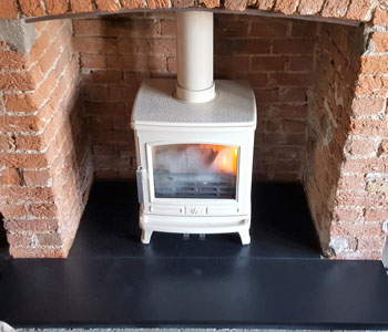 ACR Oakdale Multi-fuel Stove - in enamel buttermilk installation with black slate hearth in Bookham, near Leatherhead, Surrey.