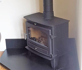 Avalon Slimline 8 Multi-Fuel Stove - fitted by our own installers with internal system chimney and corner shaped slate hearth in Banstead, near Epsom, Surrey.