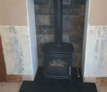 Hergom E30 XS Cast Iron Stove - with standard leg fitted by our installers with Riven slate hearth in Abinger between Guildford and Dorking in the Surrey Hills.
