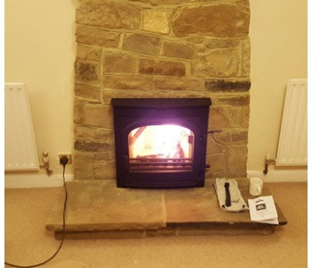 Di Lusso R5 Woodburner - with curved sides in black fitted by our installers with thermally insulated twin wall chimney system near Horsham, West Sussex.