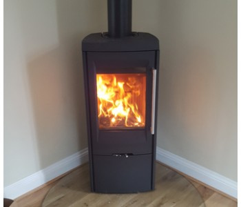 Termatech TT30G Woodburner - with side glass in black with teardrop shaped glass hearth and twin wall thermally insulated chimney system installed by our fitters near Godalming, Surrey.