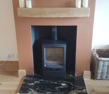 Stovax Vogue Midi Wood Stove - with plinth base and deep, rustic oak beam installed in Horley, Surrey between Redhill and Crawley.