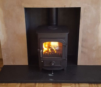 Clearview Pioneer 400 Multi-Fuel Stove - with flat top, 50mm legs in black installation with honed granite hearth and standard fascia rustic, light oak beam in Holmwood between Dorking and Horsham, West Sussex.