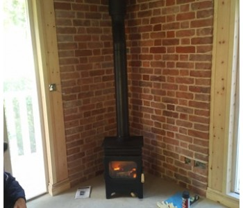 Burley Hollywell Stove - connected to a twin wall thermally insulated chimney system in a timber framed building in the Surrey Hills, near Guildford.