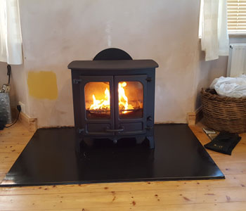 Charnwood Island 2 Stove - with low legs in black installed by our fitters with slate hearth between Esher and Kingston-upon-Thames.