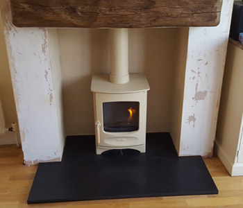 "Charnwood C4 Woodburner - in almond with a 48"" extremely aged oak beam in medium oak. Installed in Guildford, Surrey"
