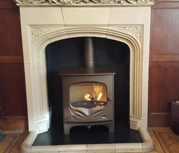 Charnwood Bembridge Woodburner - in bronze with a black slate hearth. Installed in East Horsley near Leatherhead, Surrey