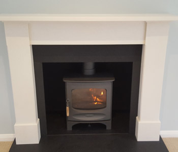 Charnwood C5 Woodburner - in gun metal with a honed granite hearth and limestone fire surround Alice in New Crème. Installed in West Clandon near Guildford, Surrey