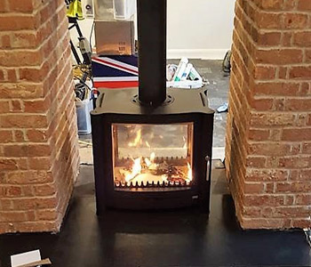 Firebelly FB2 Double Sided Stove - in black with slate hearth.  Installed in Holmbury St. Mary near Dorking, Surrey