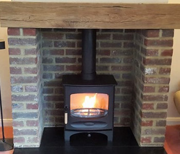 Charnwood C5 Woodburner - in black with a slate and a Bespoke oak beam, air dried. Installed in Holmbury St. Mary near Dorking, Surrey