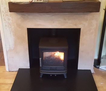 ACR Oakdale Multifuel Stove - in matt black with a slate hearth and rustic oak beam in Medium/ Dark finish. Installed in Pyrford near Woking, Surrey