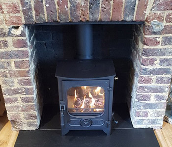 Charnwood Country 4 Woodburner - in black with riven slate hearth. Installed in Peaslake near Guildford, Surrey