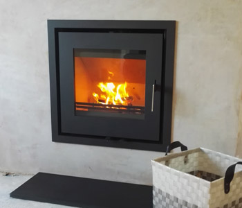 Westfire Uniq 23 Inset Stove - in black with a black honed granite hearth. Installed in Merrow near Guildford, Surrey