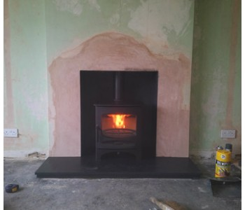 Charnwood C5 Woodburner - we raised the lintel, increased the width of the chamber; plastered, rendered and painted the chamber with heat proof paint in Charcoal; re-lined the chimney; fitted honed black granite hearths and connected the woodburner