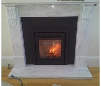 Di Luso R5 Inset Woodburner - with three sided frame in black from Hunter Stoves along with honed black granite slips and header, installed in the Surrey Hills