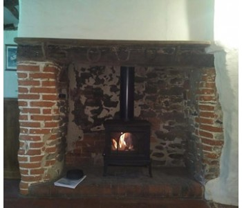 Jotul F100 Woodburning Stove - in the inglenook fireplace of a picturesque cottage set in the Surrey Hills near Cranleigh